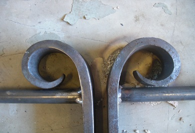 Double pig tail scrolls for meeting gate ends