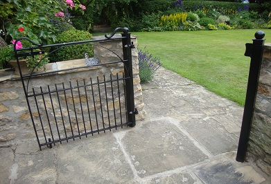 hoop braced gate with sawn off lower upright ends.  This gate has a clapping plate so as to open in one direction only  and also to aid in fastening the latch